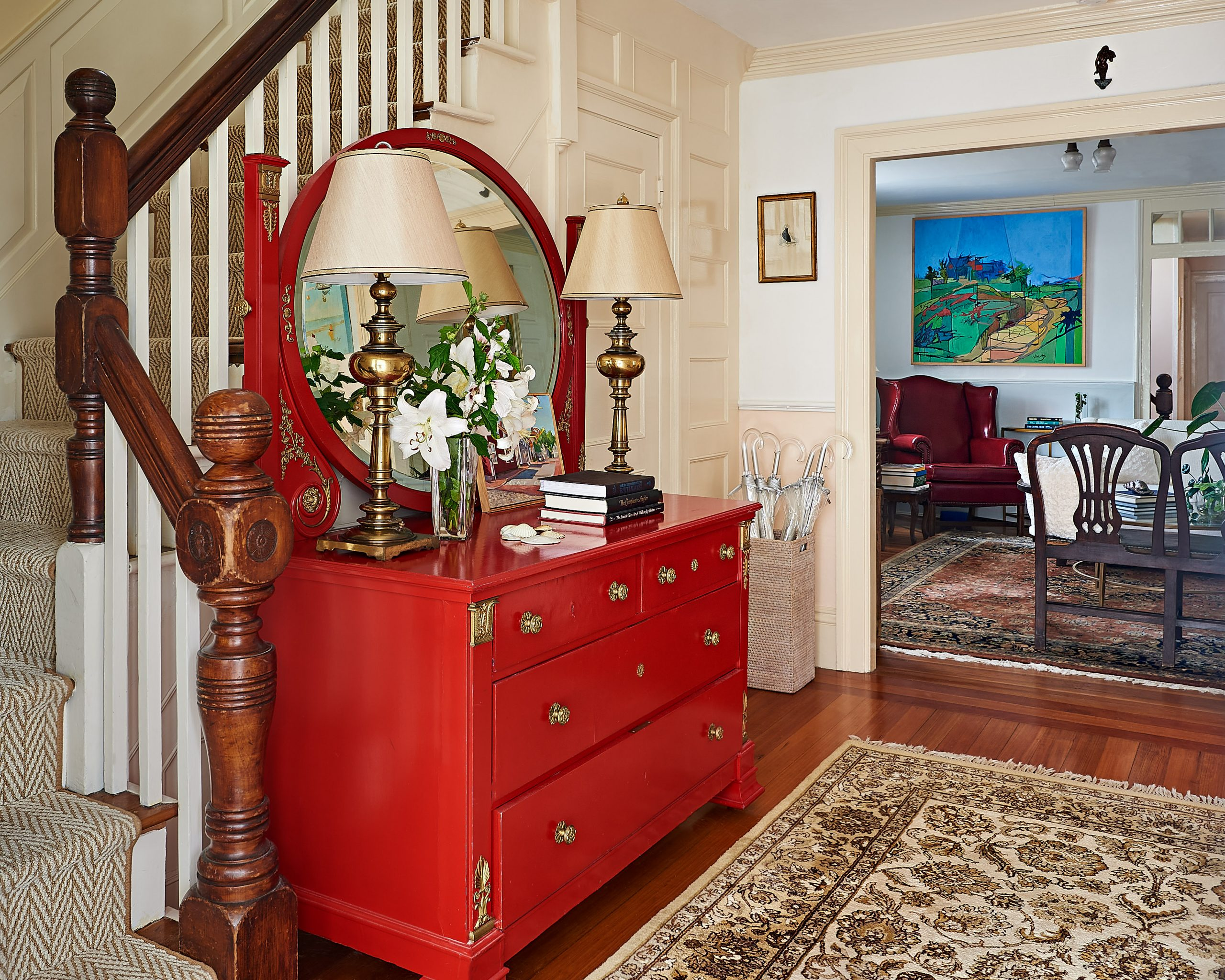 Red chest of drawers with a mirror by the stairs