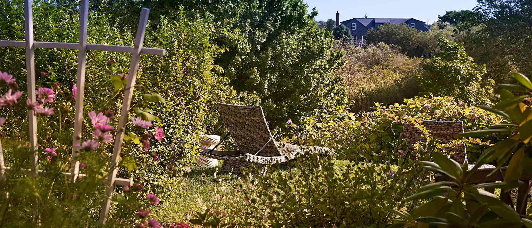 A wicker chaise lounge in the garden surrounded by grass and flowers
