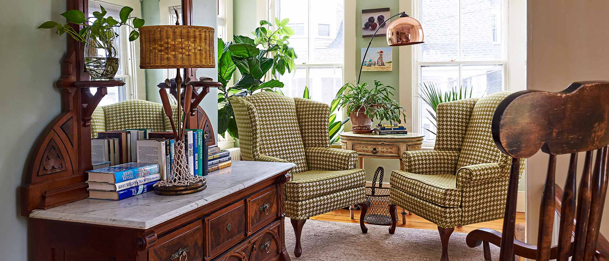 Sitting room with two chairs and antique wood dresser and airy bright windows